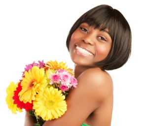 smiling african american woman holding a bouquet of flowers