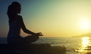 silhouette of a woman sitting in lotus position