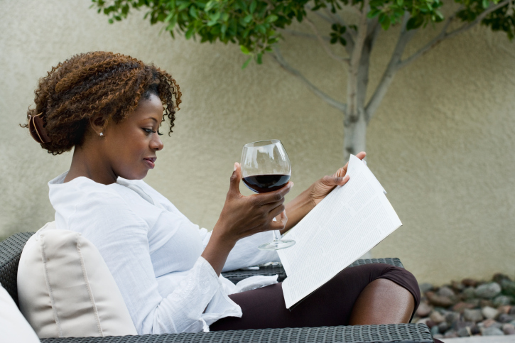 African woman reading on patio and drinking red wine