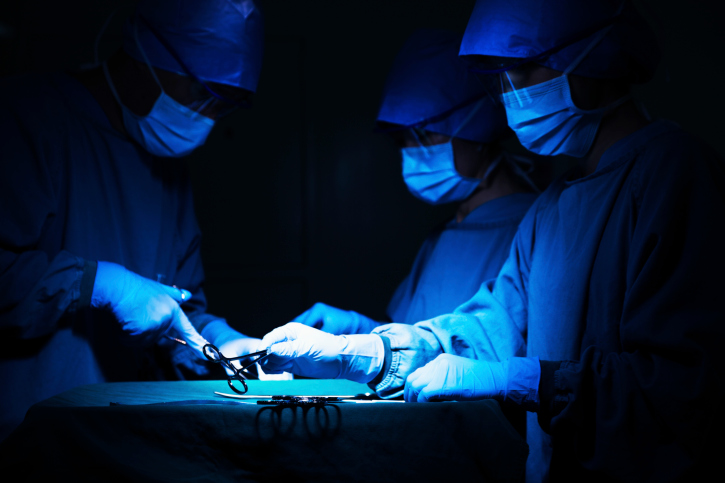 Surgeons holding surgical equipment at the operating table and working