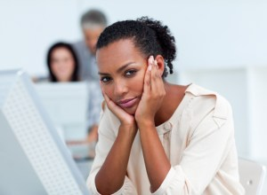 african american woman looking upset while sitting at a desk