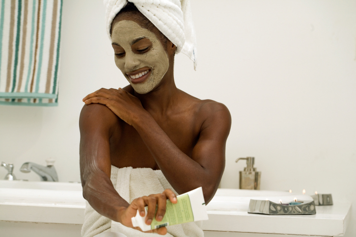 woman with face mask putting on lotion