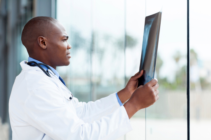 black doctor looking at x-ray