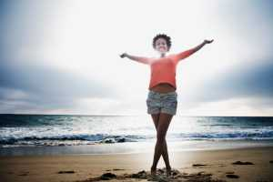 african american woman smiling on beach