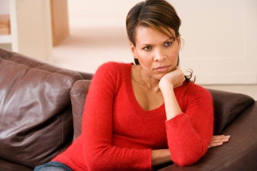 Depressed woman sitting on couch