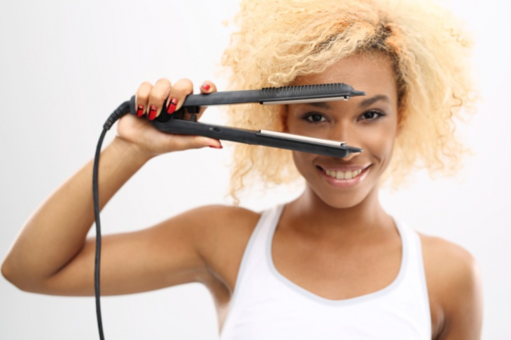 woman using flat iron on hair