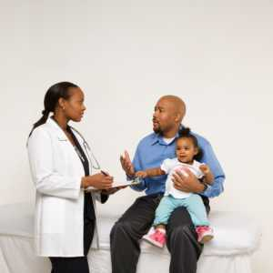 father with baby talking to doctor