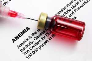 vial with needle sitting on top of a paper with the description of anemia typed on it