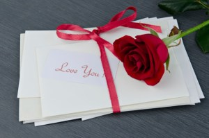 love letter wrapped in red ribbon with rose