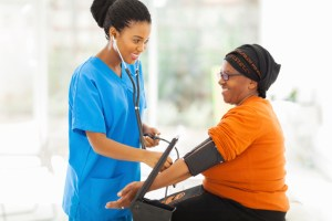 nurse taking womans blood pressure