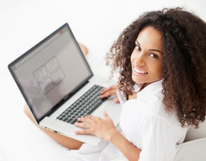 african american woman sitting with laptop on her lap