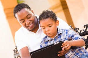 African American Black Father and Son Using Touch Pad Computer Tablet