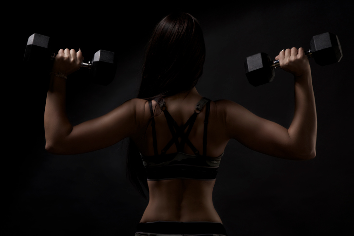 strong tanned beautiful sports girl on a black background.