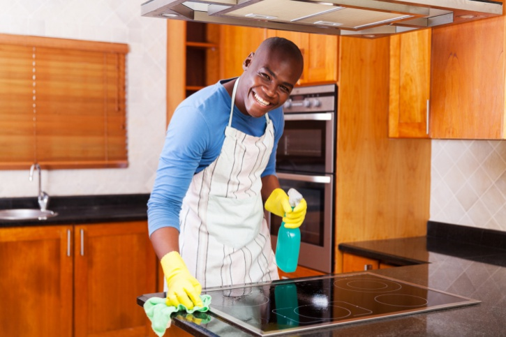 African American Black man cleaning kitchen stove