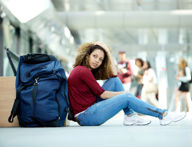 young African American woman sitting air airport duffle bag