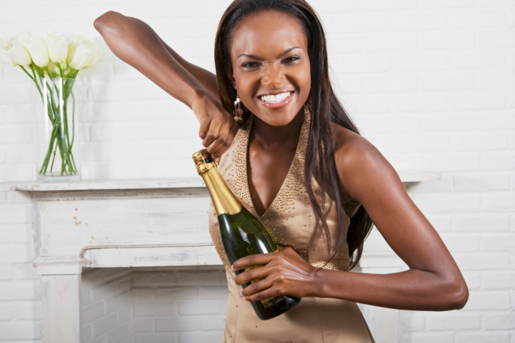 Young African American Black Woman Opening Bottle of Champagne