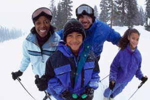 African American Black parents with two children in snow skiing
