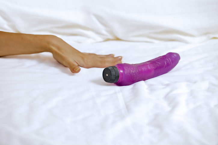 Woman's hand reaching for dildo in bed