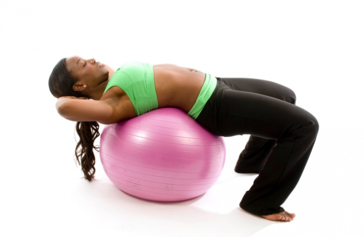 African American woman doing crunches on stability ball