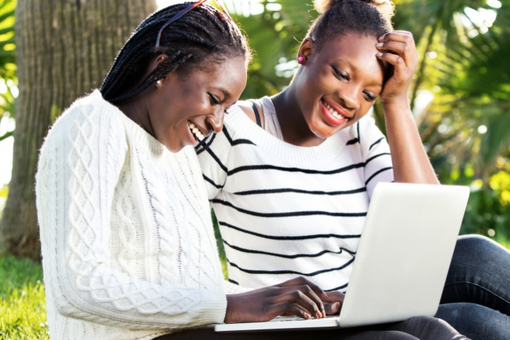 African American teen girls on laptop outside