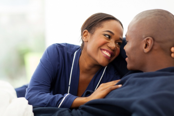 Happy African American couple flirting in bed