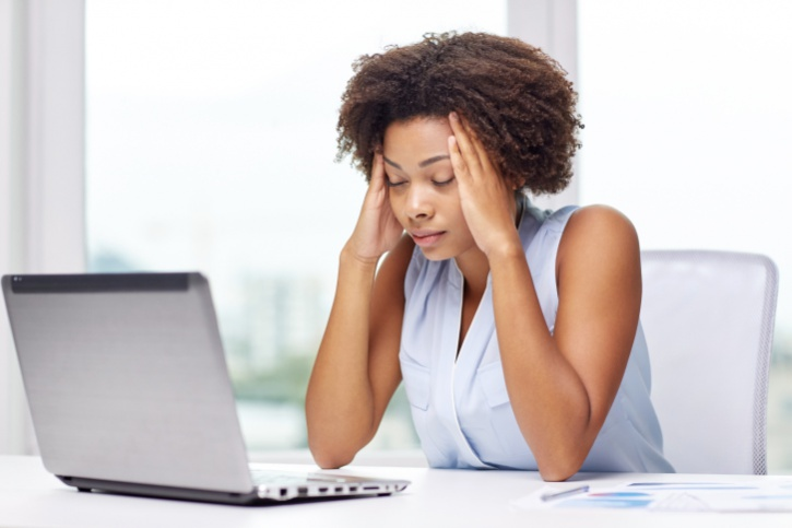 African American woman with headache on laptop
