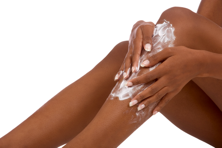 female putting Moisturizer on her legs (close up)