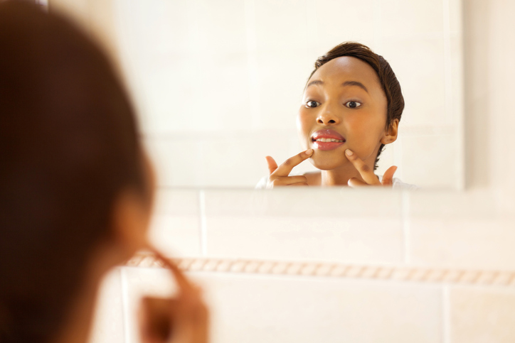 African American woman checking face for pimples in mirror