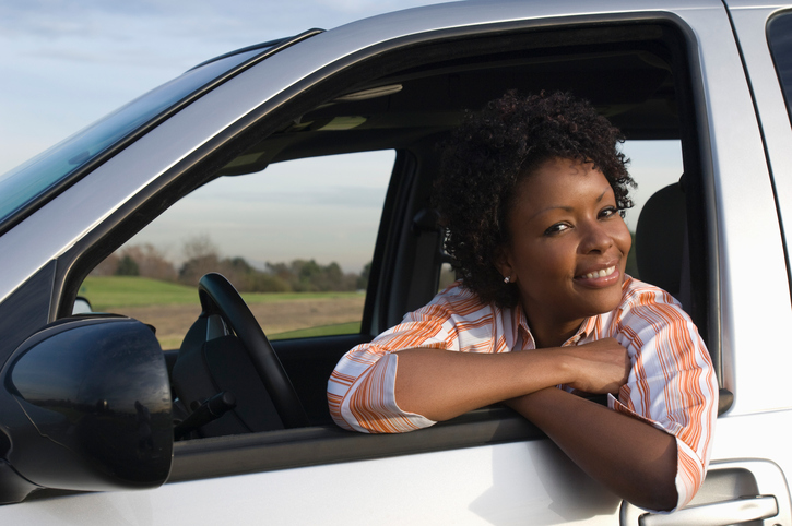African American woman leaning out car window smiling