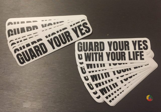 picture of a laptop with two stacks of stickers. one is printed with Guard Your Yes and the other is printed with Guard Your Yes With Your Life