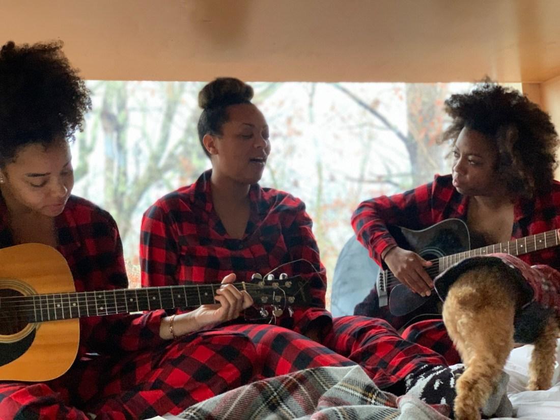 Three women in matching pajamas with guitars