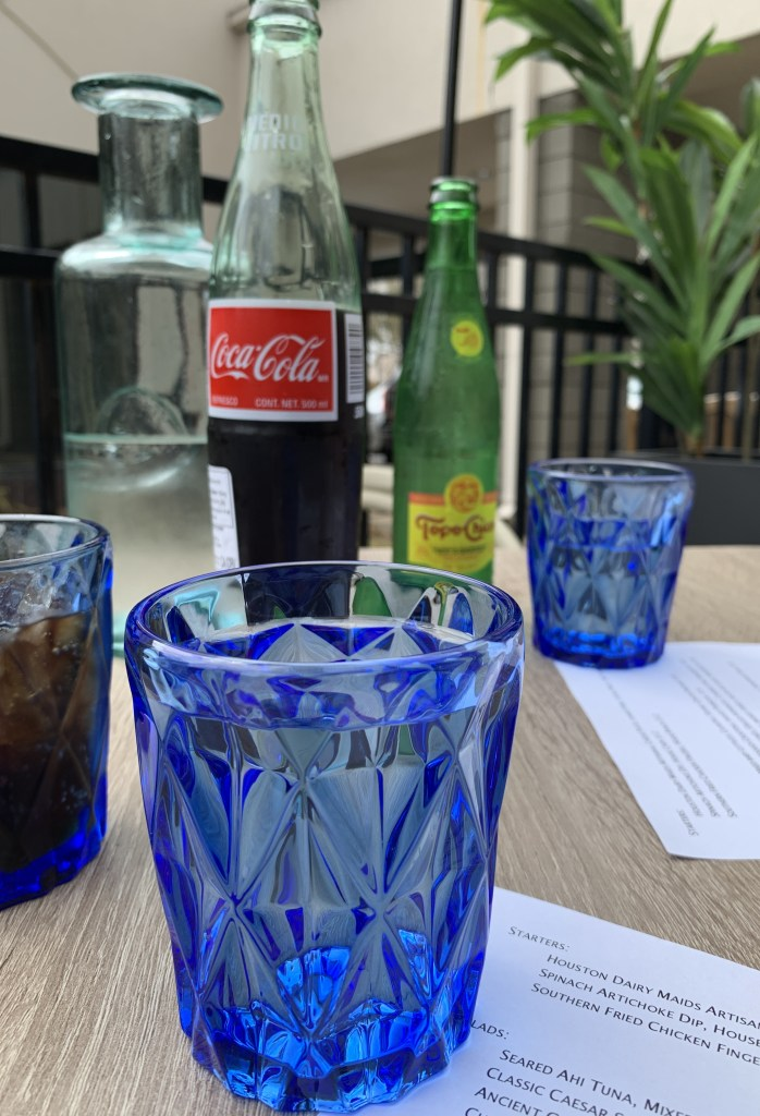 Table with Coke, Topo Chico and blue water glasses