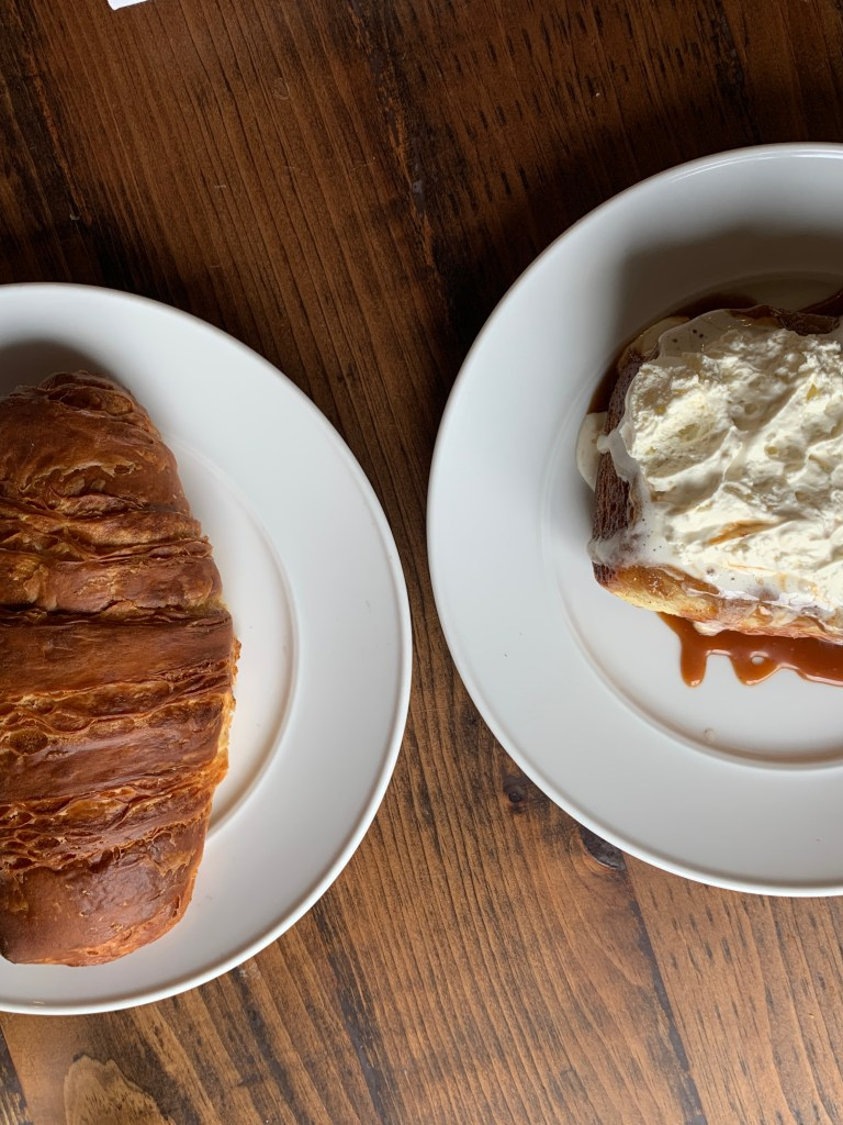 A croissant on a white plate and a cinnamon roll on a white plate