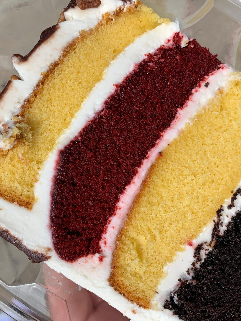 Layered cake with chocolate layer, yellow layer, red velvet layer, and another yellow later.  White icing.