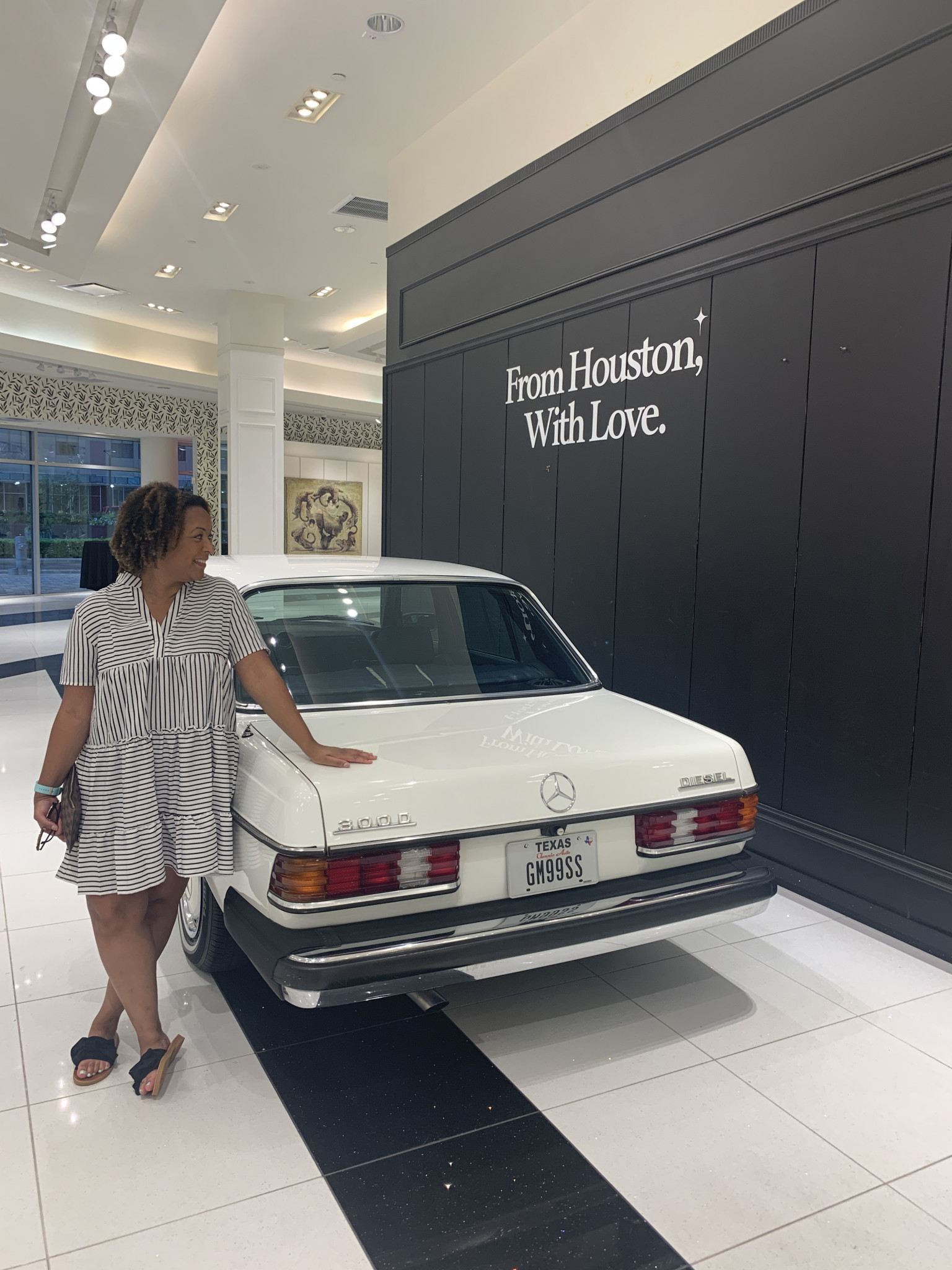 """Woman standing next to a white mercedes with """"From Houston With Love"""" on the wall"""