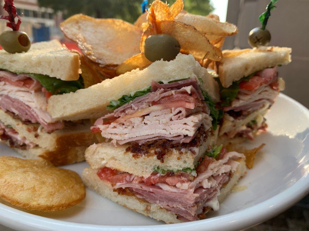 Club sandwich topped with potato chips