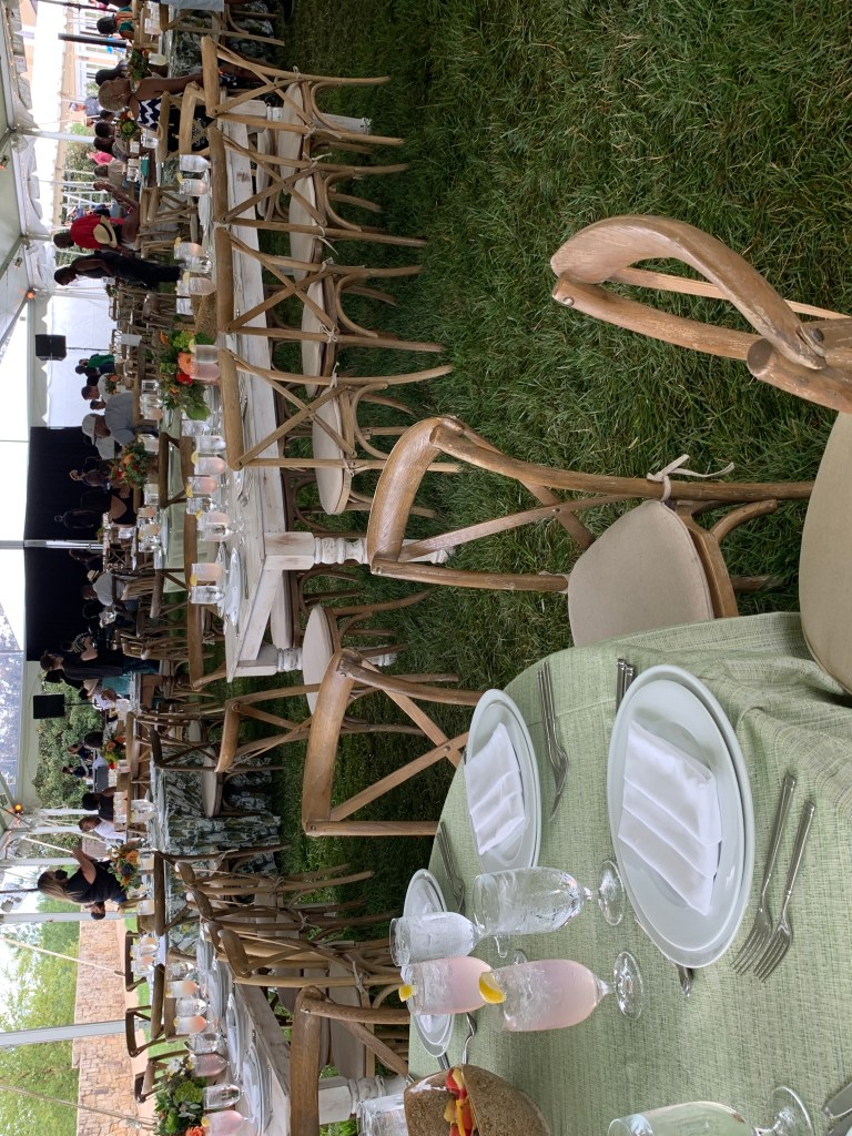 Tented area with dining tables covered with green table clothes and place settings with chairs as well