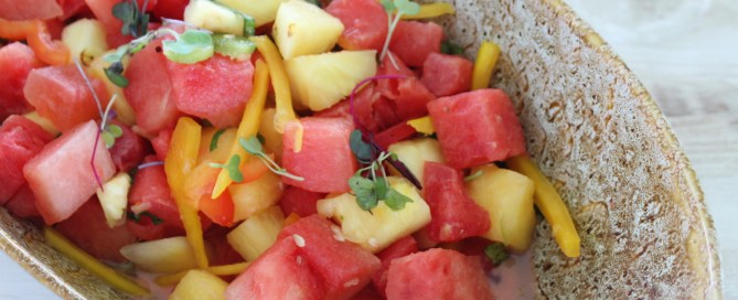 Fruit salad in a bowl with watermelon and melons with a metal spoon
