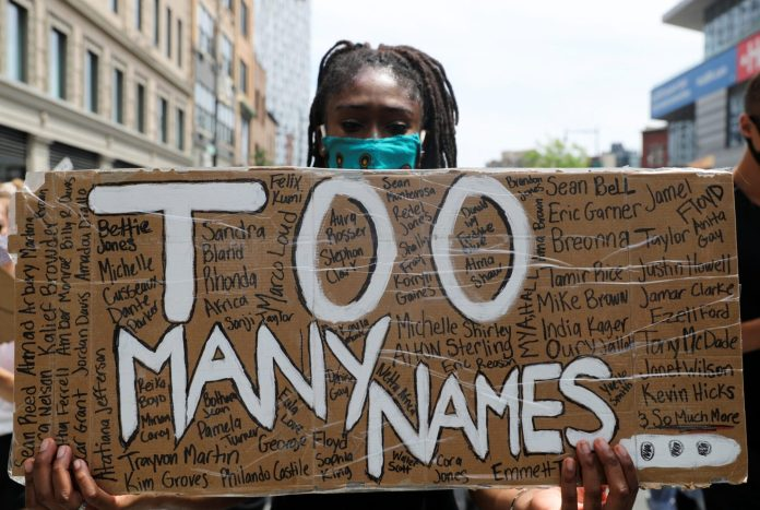 a protestor with a sign that says too many names