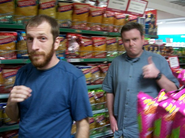 Two white men in a grocery store without masks.