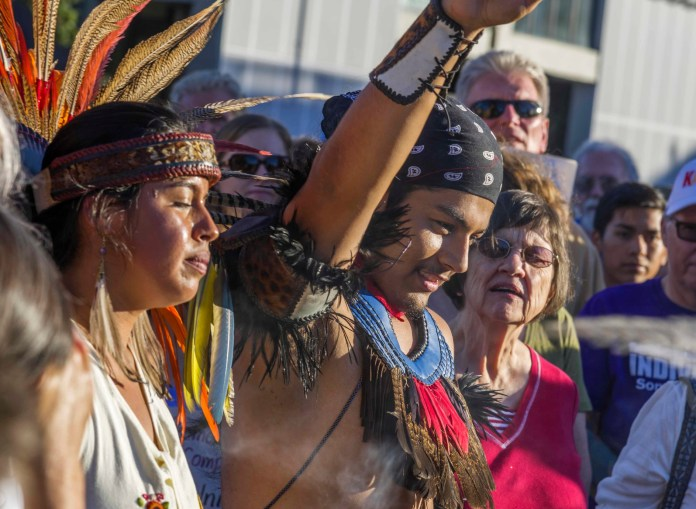 Indigenous man and woman with fist at protest with colonizers in the background.