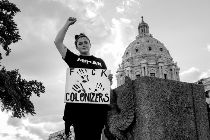 A demonstrator stands beside the place where a Christopher Columbus statue stood at the State Capitol in St Paul, Minnesota. Her sign reads 'Fuck Colonizers'.