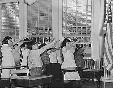 Students pledging allegiance to the American flag with the Bellamy fascist salute.
