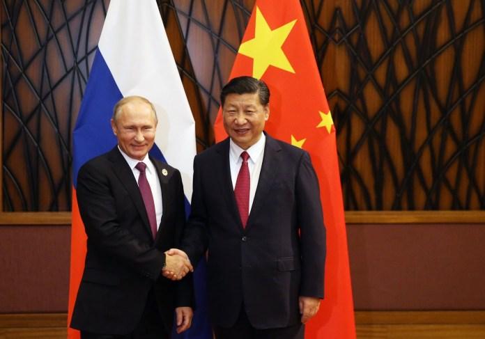 Xi Xin Ping and Putin shaking hands
