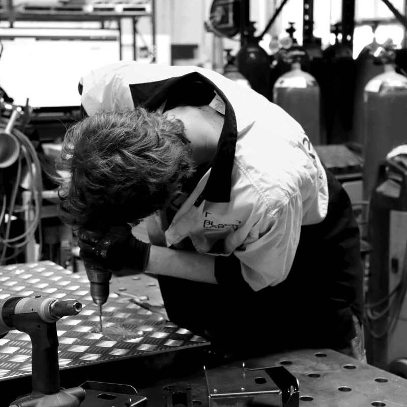 black and white image of man assembling parts