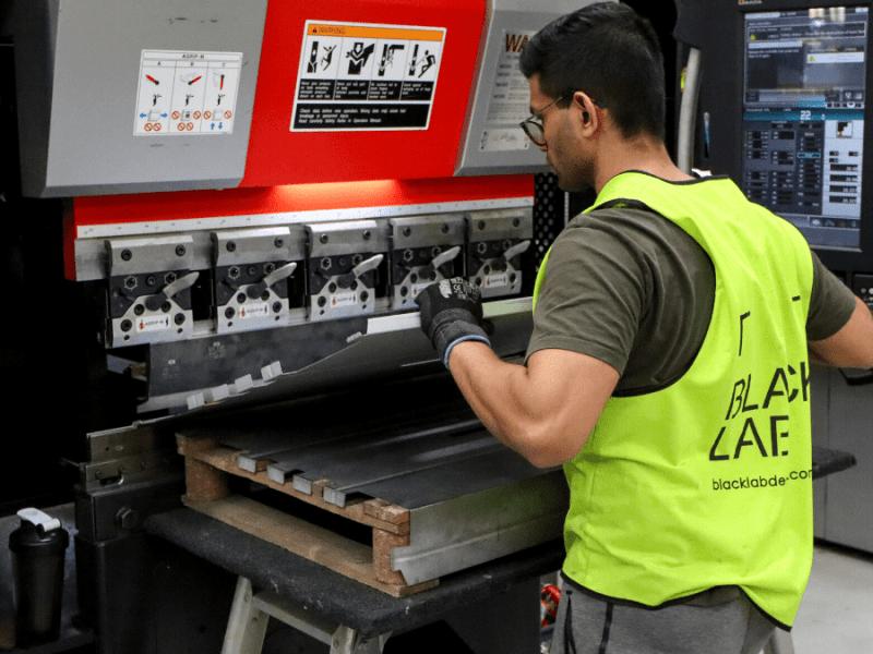 a man bending metal on a press machine