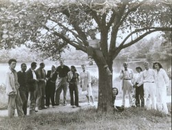 "Summer Arts Institute Faculty, Black Mountain College, 1946. Left to right: Leo Amino, Jacob Lawrence, Leo Lionni, Ted Dreier, Nora Lionni, Beaumont Newhall, Gwendolyn Lawrence, Ise Gropius, Jean Varda (in tree), Nancy Newhall (sitting), Walter Gropius, Mary ""Molly"" Gregory, Josef Albers, Anni Albers. Courtesy of Western Regional Archives."