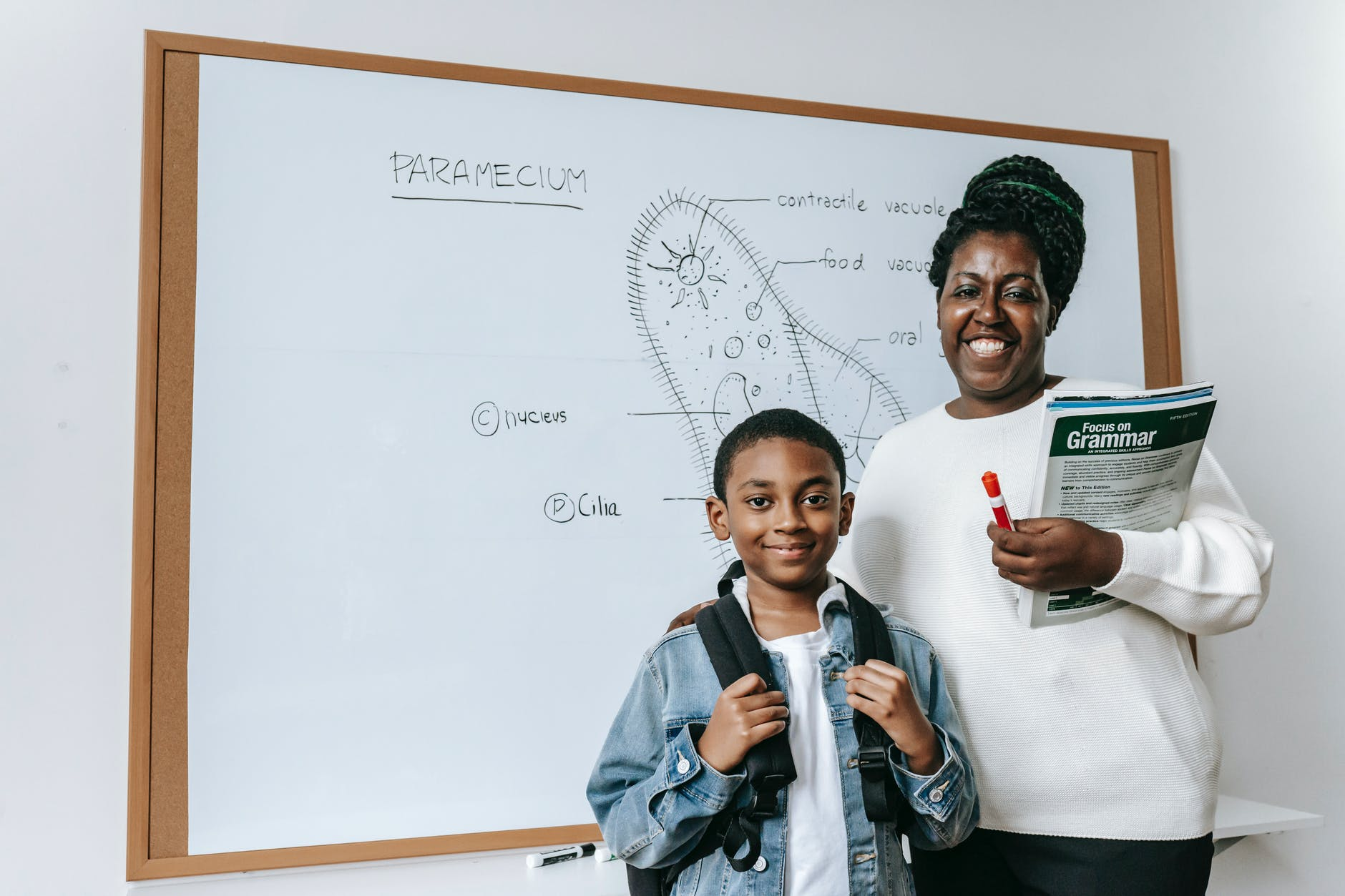 cheerful black woman with student against whiteboard
