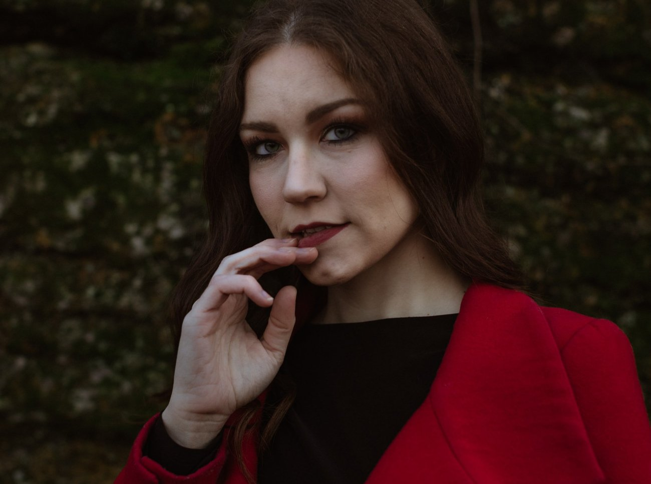 Woman with red coat and lipstick touches lips