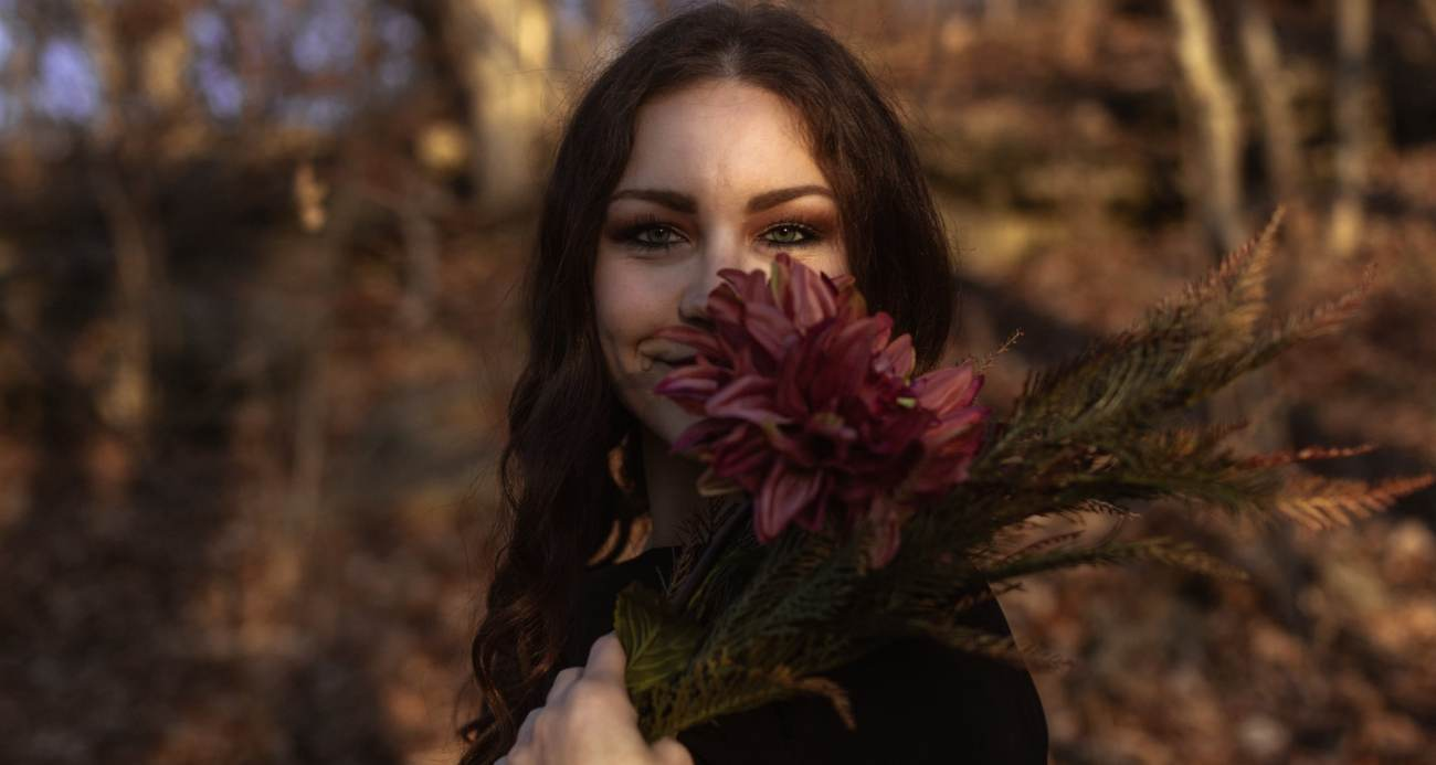 Girl hold large pink flower by her face at golden hour